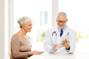 smiling senior woman and doctor with tablet pc